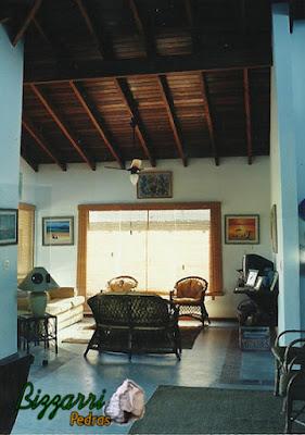 Vista da sala de estar com o piso de cimento queimado branco com o forro de madeira de Ipê por cima dos caibros e nas paredes a massa de mão única desempenada e filtrada em construção de casa em Ubatuba-SP.