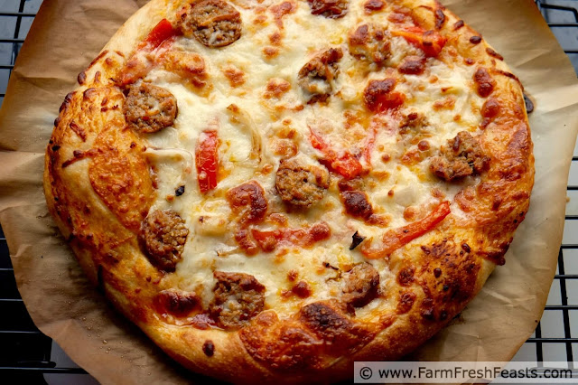 an overhead image of a grilled sausage and peppers pizza