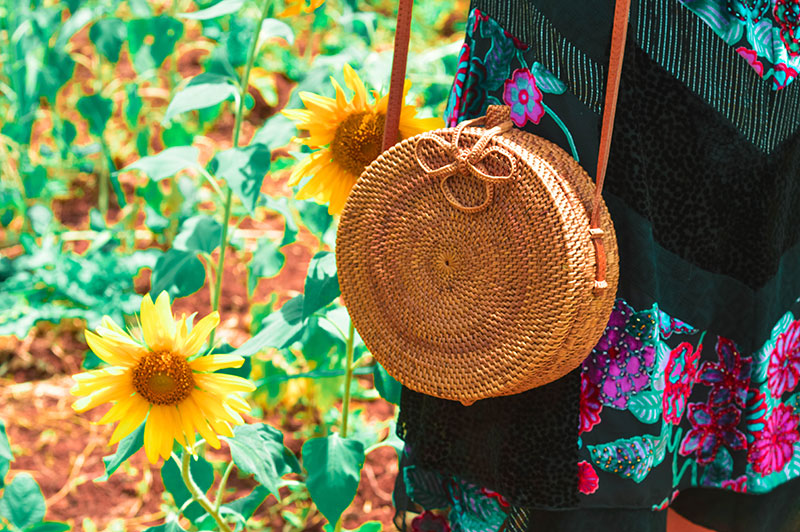 round rattan straw fibre basket bag in sunflower field outfit details