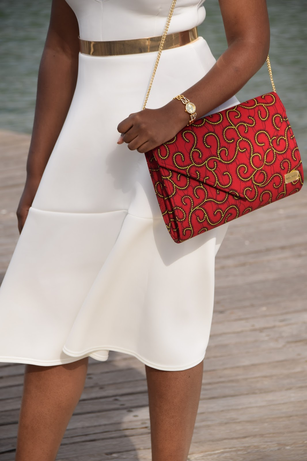 white headscarf paired with white ruffle blouse, gold belt and ankara envelope handbag