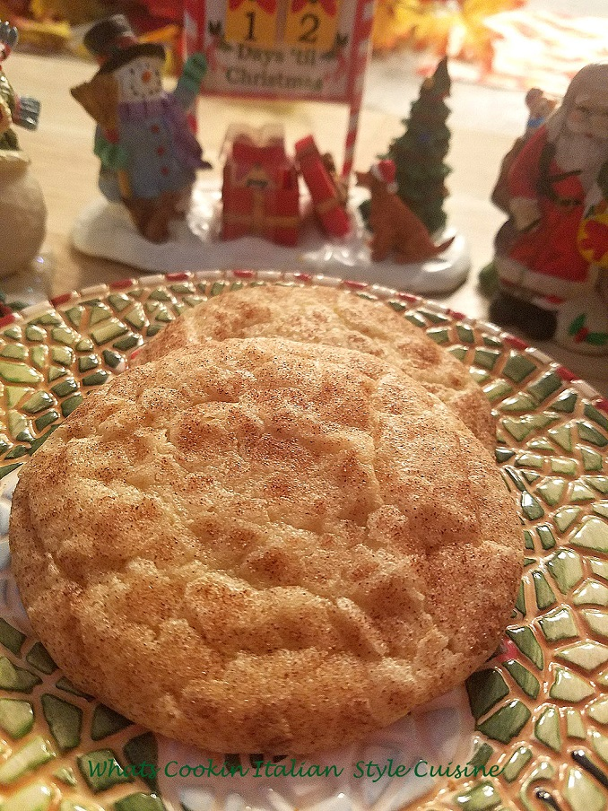 these are a cinnamon sugar cookie with a delicious outer crispy cinnamon coating baked on. This is how to make the best ever snicker doodle cookies. These cookies are on a pretty Christmas plate that says ho ho ho and Christmas santa cookie decorations are in the background,