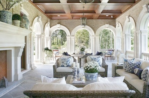 Magnificent loggia with stone fireplace blue and white decor and archways by Enchanted Home