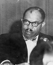 Candid shot of a middle-aged Black man with a receeding hairline, dark-rimmed eyeglasses, and a short moustache