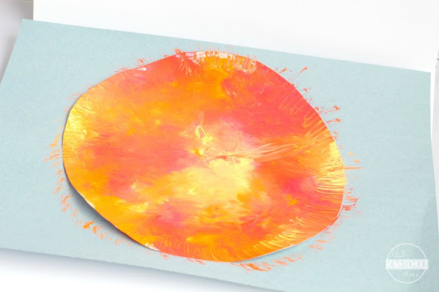 glue sun craft to blue paper and use a paint brush to make sun bursts