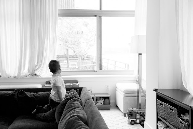 son looking out the window in black and white