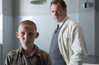 A young boy with shaved head Ernst Lossa (Ivo Pietzcker)  is being viewed by a doctor Dr. Werner Veithausen (Sebastian Koch) standing behind him. Courtesy of StudioCanal.