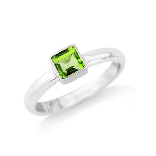 Peridot ring set in gold on a silver band