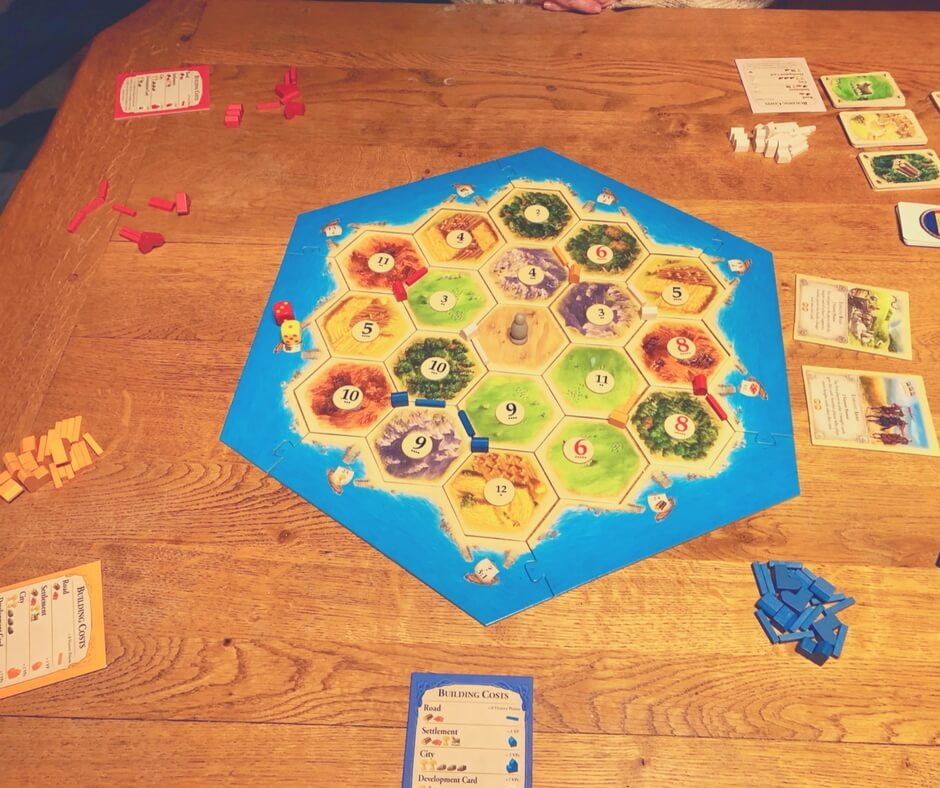 "Small houses have been put onto the Catan board, they are in colours, red, blue, white, and orange. There's a grey figure in the centre of the board, this is the ""robber""."