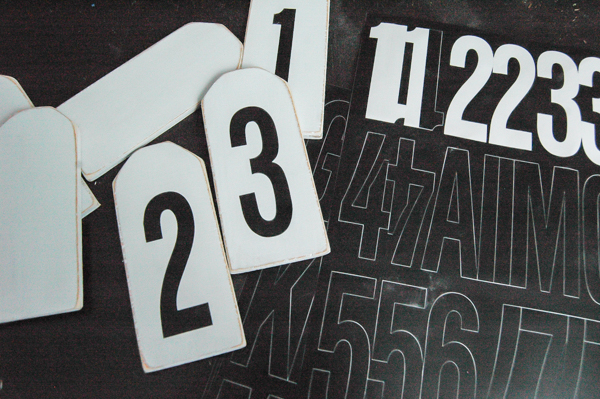 Applying vinyl numbers to distressed number tags.