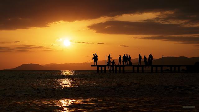 Pier met mensen bij ondergaande zon.