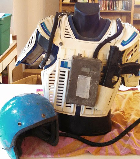 Battered white battle suit with blue accents prior to cleaning