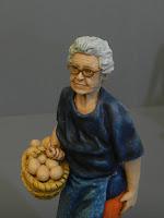 statuetta ritratto signora anziana vecchietta occhiali cesto uova orme megiche