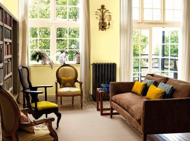 Decoración de sala con paredes amarillas y muebles marrones Un
