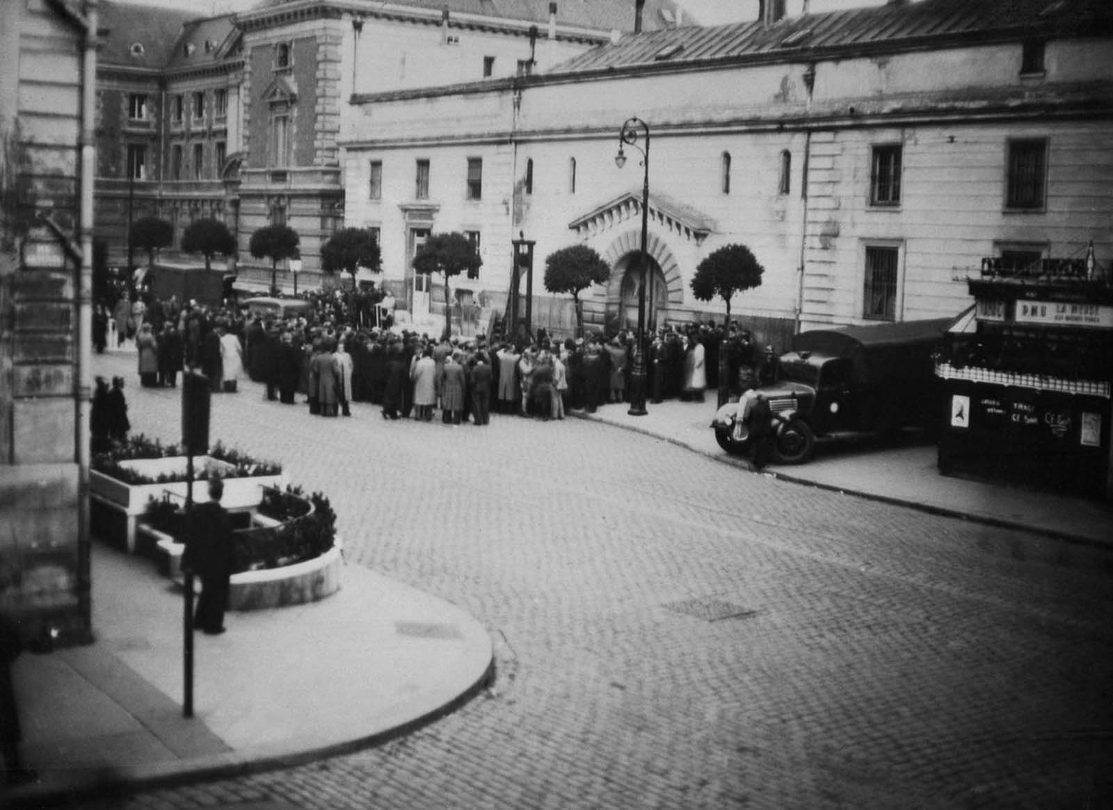 A crowd awaiting Weidmann's execution gathers around the guillotine outside the Prison Saint-Pierre.