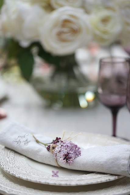 dishes with white roses and purple wine stems and lilac