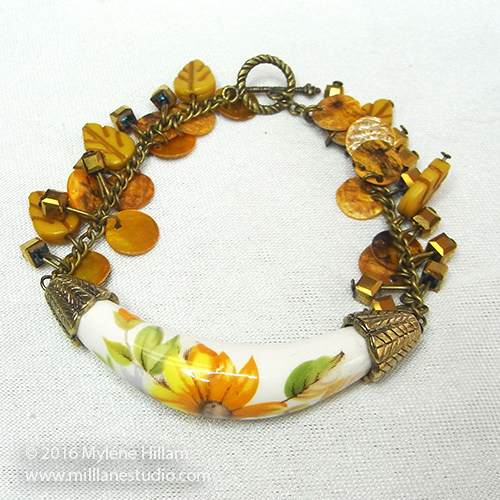 Floral yellow bracelet with a curved tubular bead and a pre-strung strand of yellow beads