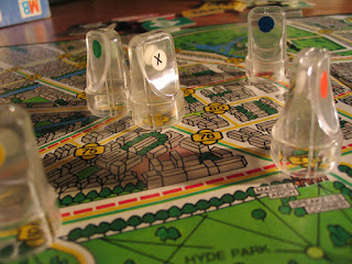 The five clear, colourless plastic pawns from the Scotland Yard board game, on the game board. The board is a stylised map of London, with various street intersections labelled with a number. These numbers are connected by one or more lines of green, yellow, and/or red. The pawns each have a coloured dot to indicate which player's they are, except the one in the centre, belonging to Mr X, which has a white dot marked with a black X.