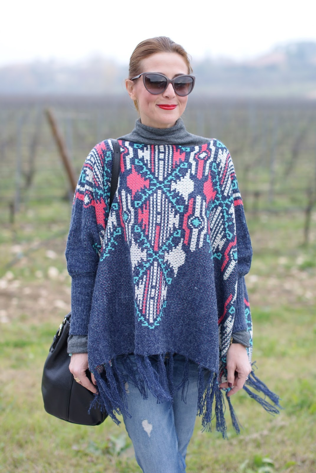 Fringed aztec poncho and boyfriend jeans for a western inspired outfit on Fashion and Cookies fashion blog, fashion blogger style
