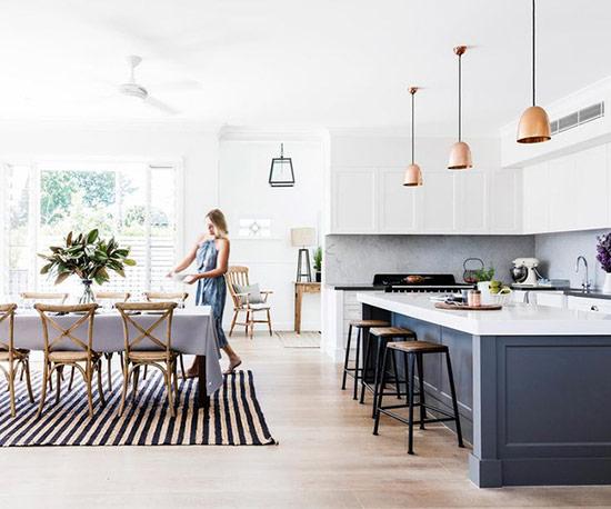 Phòng bếp hiện đại màu trắng và không gian phòng ăn theo phong cách rustic với những chiếc ghế gỗ theo phong cách chiết trung đáng yêu.