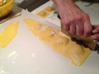 image of pasta sheet with filled ravioli. Ravioli are being cut apart after they've been sealed.