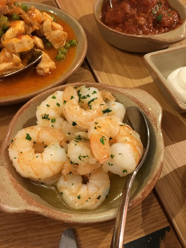 a dish of prawns with other dishes just visible in the background