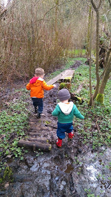 two toddlers playing outside in the woods