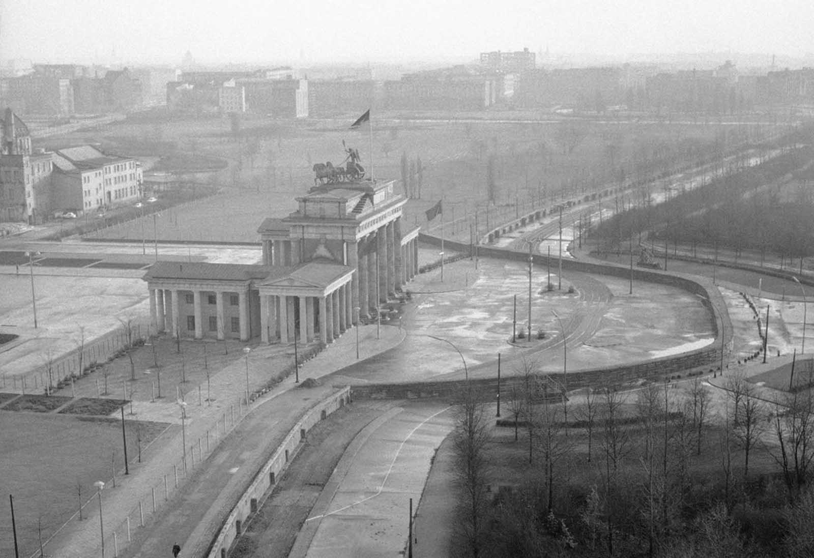 View from top of the old Reichstag building of the Brandenburg Gate, which marks the border in this divided city. The semi-circled wall around the Brandenburg Gate was erected by East German Vopos on November 19, 1961.