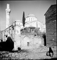 Zeyrek Kilise Camii (Monastery of Christ Pantocrator), as seen from the southwest, March 1936. The former triptych church of the 12th century, which in 1936 served as a mosque, was in a deprived neighborhood. Pictured are children playing, a woman with a black scarf carries water and a wooden house - probably the house of a Turkish imam- abuts the medieval structure [Credit: © Nicholas V. Artamonoff Collection, Image Collections and Fieldwork Archives, Dumbarton Oaks]
