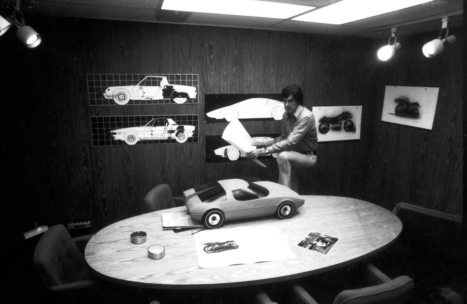John DeLorean with various car sketches and models in a conference room in his office. 1974.