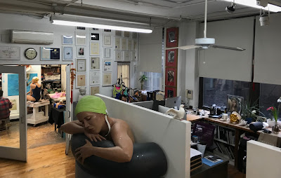 A studio office with a larger than life sculpture of a woman in the foreground.