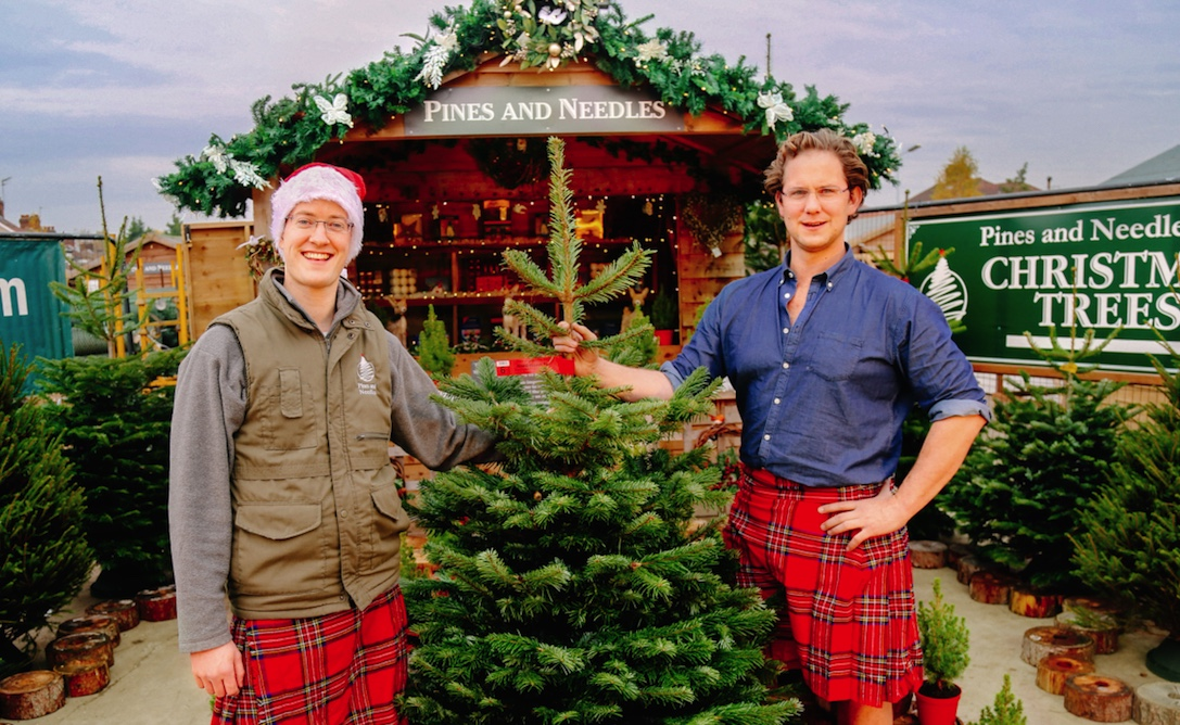 Guys in kilts with a Christmas tree at a tree farm