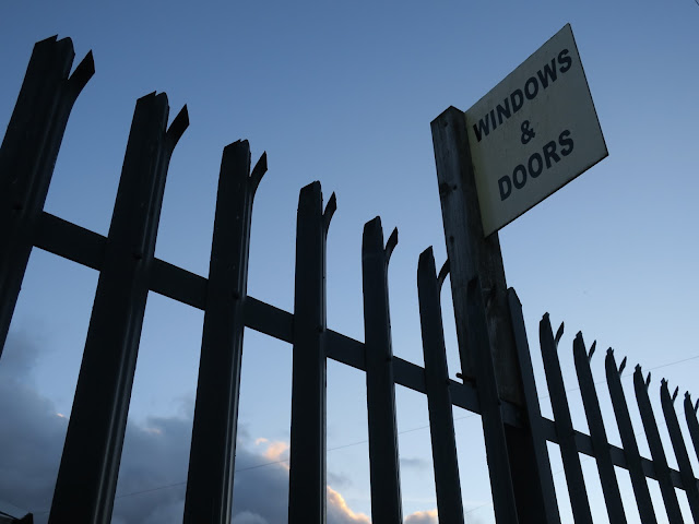 Sign advertising Windows and Doors attached to metal fence.