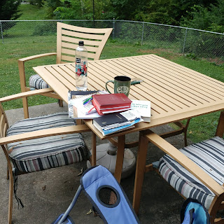 Outdoor table with prayer books, journal, coffee cup and water bottle