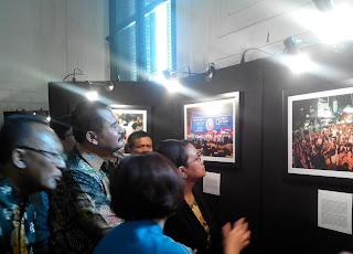 Bu Retno mengamati foto-foto lainnya
