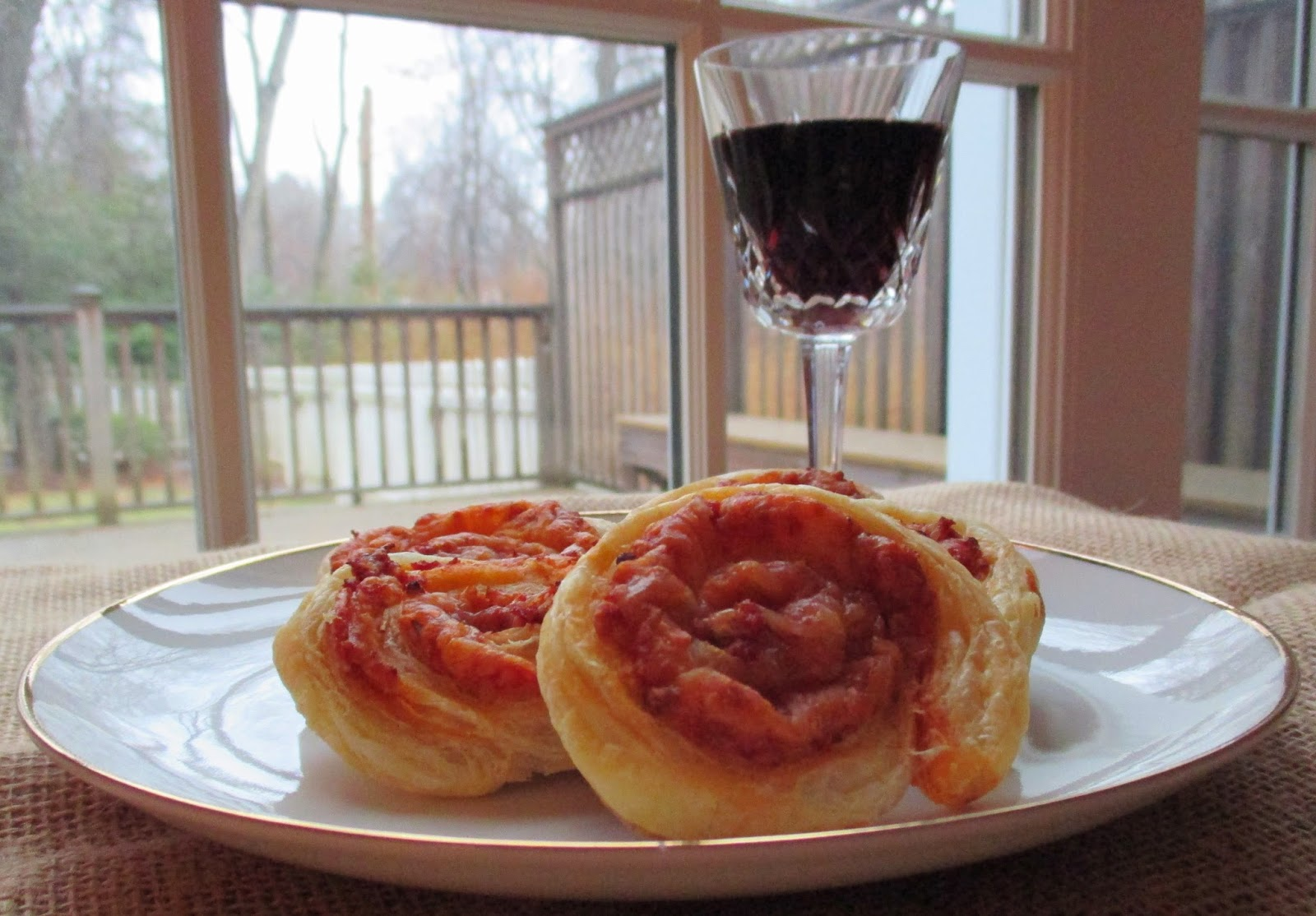 tomato and cheese pinwheels with a glass of red wine