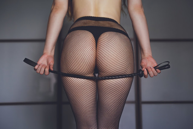 dominant woman with riding crop, bdsm. Beautiful woman ass in fishnet stockings and whip. Strict woman domination