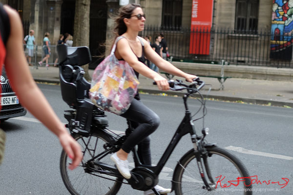 Bike with empty child's seat; woman in jeans and singlet, seethrough floral bag over shoulder. Paris photos by Kent Johnson for Street Fashion Sydney.