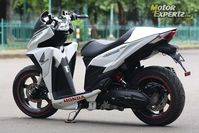 Foto Modifikasi keren Honda Vario Techno dengan merubah stang dan didominasi warna putih serta merubah knalpot menghilangkan shockbreaker pada motor ban motor diubah dengan ukuran yang besar