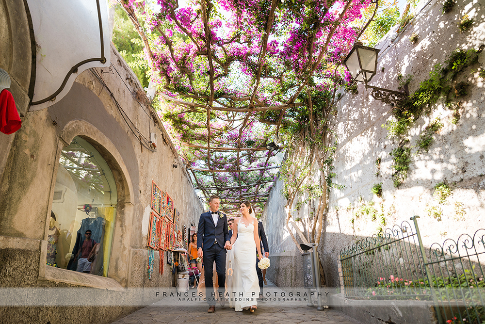 Bride and groom walking under bougainvillea