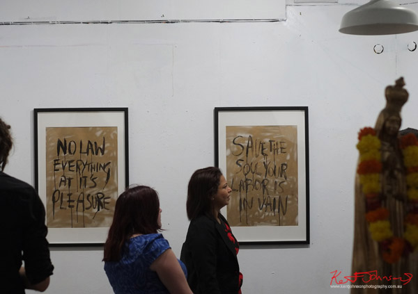 Paintings by Joanna Frank with hand lettered slogans in gold and black. Photographed by Kent Johnson for Street Fashion Sydney.