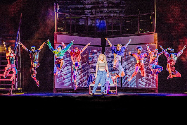 joanne clifton stands centre stage while 8 dancers behind her leap in the air, arms outstretched