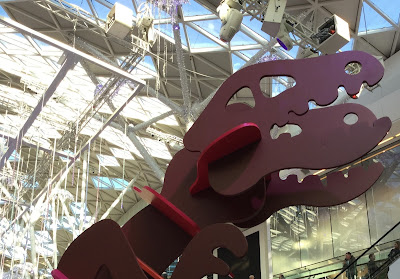 Pic of huge head of cut-out dinosaur figure against bright glass shopping centre roof