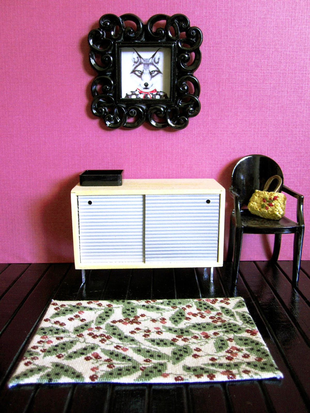 Modern doll's house miniature hallway with black floorboards and berry-coloured wall. On the floor is a cream rug with a pattern of leaves and berry stalks in soft greens,  berry colours and black.