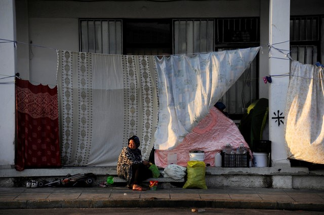 A woman sits and looks on outside a building covered up with sheets to protect the dwellers from the strong summer sun outside of the disused Hellenikon airport, where stranded refugees and migrants are temporarily accommodated in Athens, Greece, August 10, 2016. REUTERS/Michalis Karagiannis