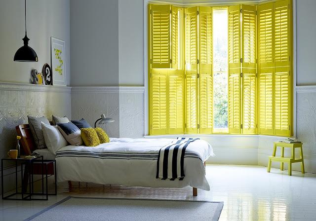 Żółte okiennice wewnętrzne drewniane w sypialni