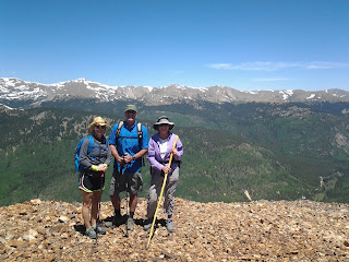 Sunny day with three hikers standing at the edge of a rocky trail with snow peaked mountains in the distance.