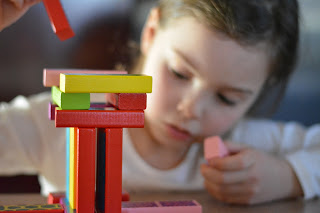 child building with multi-colored blocks