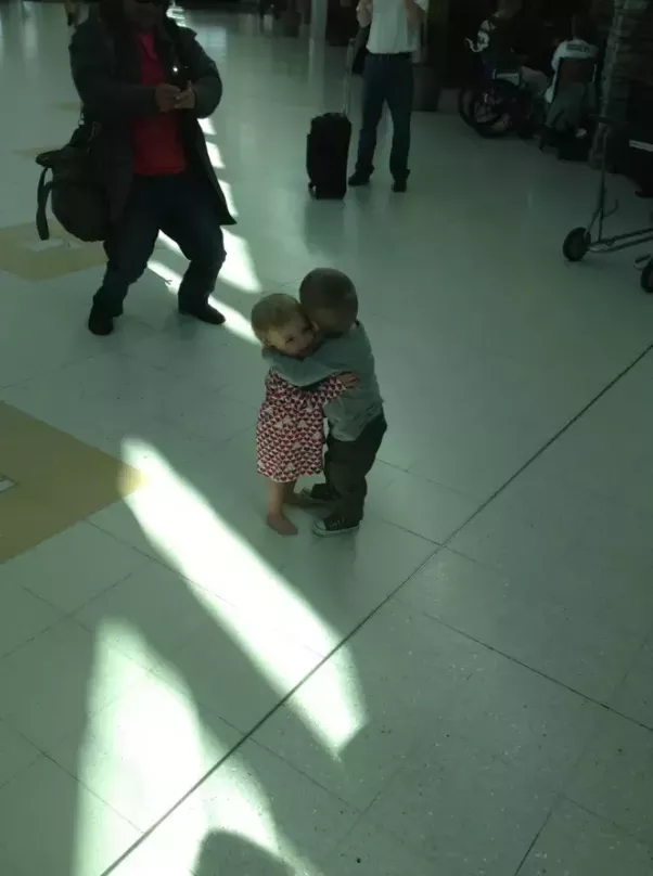 These two babies were complete strangers, but they decided to give each other a big hug at the airport.