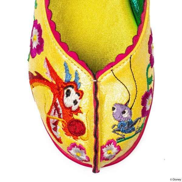 close up of toe of shoe in yellow with embroidered Cri Kee and Mushu figures from Mulan