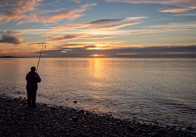 Photo of a fisherman on Maryport beach at sunset